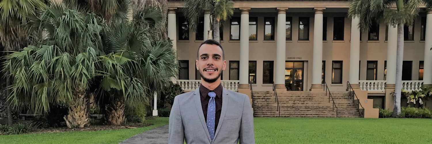 Photo Of Student Standing In Front Of Hawaiʻi Hall